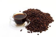 Μαύρος καφές σε ένα φλυτζάνι γυαλιού και τα σιτάρια του καφέ σε ένα άσπρο υπόβαθρο Στοκ Εικόνα
