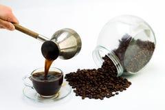 Μαύρος καφές σε ένα φλυτζάνι γυαλιού και τα σιτάρια του καφέ σε ένα άσπρο υπόβαθρο Στοκ εικόνες με δικαίωμα ελεύθερης χρήσης