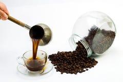 Μαύρος καφές σε ένα φλυτζάνι γυαλιού και τα σιτάρια του καφέ σε ένα άσπρο υπόβαθρο Στοκ Εικόνες