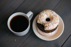 Μαύρος καφές σε μια άσπρη κούπα και τρία donuts σε ένα πιάτο Στοκ Φωτογραφία