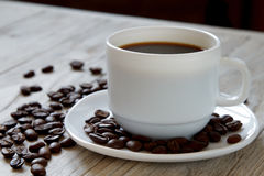 Μαύρος καφές σε μια κούπα και ψημένα φασόλια στο ξύλινο suface Στοκ φωτογραφία με δικαίωμα ελεύθερης χρήσης