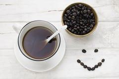 Μαύρος καφές στα άσπρα φασόλια φλυτζανιών και καφέ με το κουτάλι στοκ εικόνα με δικαίωμα ελεύθερης χρήσης
