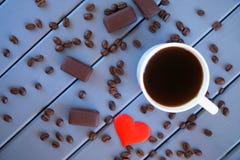 Μαύρος καφές στις καραμέλες άσπρων κουπών και σοκολάτας σε έναν πίνακα των χρωματισμένων ξύλινων πινάκων στοκ εικόνα