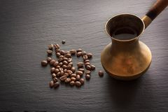Μαύρος καφές στον παλαιό χαλκό cezve και φασόλια καφέ στη μαύρη πλάκα ως υπόβαθρο με το διάστημα αντιγράφων Στοκ Εικόνες