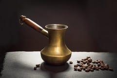 Μαύρος καφές στον παλαιό χαλκό cezve και φασόλια καφέ στη μαύρη πλάκα ως υπόβαθρο με το διάστημα αντιγράφων Στοκ Φωτογραφίες