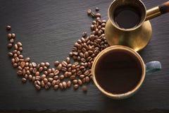 Μαύρος καφές στον παλαιό χαλκό cezve και φασόλια φλυτζανιών και καφέ στη μαύρη πλάκα ως υπόβαθρο με το διάστημα αντιγράφων Στοκ εικόνα με δικαίωμα ελεύθερης χρήσης