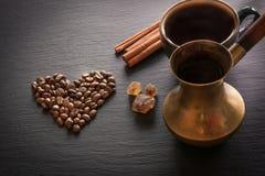 Μαύρος καφές στον παλαιό χαλκό cezve και φασόλια φλυτζανιών και καφέ στη μαύρη πλάκα ως υπόβαθρο με το διάστημα αντιγράφων Στοκ Εικόνα