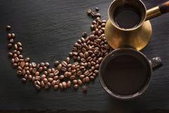 Μαύρος καφές στον παλαιό χαλκό cezve, το φλυτζάνι και τα φασόλια καφέ στη μαύρη πλάκα ως υπόβαθρο με το διάστημα αντιγράφων Στοκ εικόνες με δικαίωμα ελεύθερης χρήσης