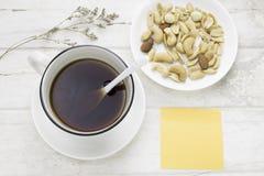 Μαύρος καφές στο άσπρο φλυτζάνι και μικτά καρύδια με το άσπρο κουτάλι στοκ φωτογραφία