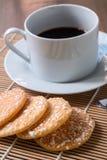 Μαύρος καφές στο άσπρο φλυτζάνι και τριζάτες κροτίδες ρυζιού με στο woode Στοκ Φωτογραφία