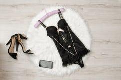 Μαύρος κορσές δαντελλών, παπούτσια και έξυπνο τηλέφωνο σε μια άσπρη γούνα Μοντέρνη έννοια, τοπ άποψη στοκ εικόνες με δικαίωμα ελεύθερης χρήσης
