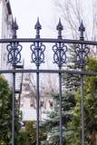 Μαύρος μεταλλικός σφυρηλατημένος φράκτης στον κήπο με τις ακίδες Στοκ Εικόνα