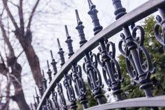 Μαύρος μεταλλικός σφυρηλατημένος φράκτης στον κήπο με τις ακίδες Στοκ Εικόνες