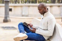 Μαύρος νεαρός άνδρας που εξετάζει τον υπολογιστή και το smartphone ταμπλετών Στοκ Εικόνες