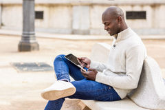 Μαύρος νεαρός άνδρας που εξετάζει τον υπολογιστή και το smartphone ταμπλετών Στοκ εικόνες με δικαίωμα ελεύθερης χρήσης