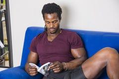 Μαύρος νεαρός άνδρας που διαβάζει στο σπίτι ένα βιβλίο Στοκ Φωτογραφίες