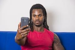 Μαύρος νεαρός άνδρας που παίρνει selfie τη φωτογραφία στον καναπέ στοκ φωτογραφίες