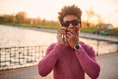 Μαύρος νεαρός άνδρας στο τηλέφωνο που γελά υπαίθρια Στοκ εικόνα με δικαίωμα ελεύθερης χρήσης