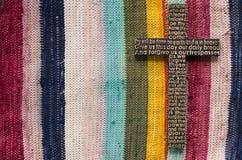 Μαύρος ξύλινος σταυρός με την προσευχή Λόρδου ` s στο επάνω χρωματισμένο υπόβαθρο ταπήτων Στοκ Φωτογραφίες