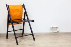 Μαύρος ξύλινος προσροφητικός άνθρακας που στέκεται κοντά στον τοίχο με το πορτοκαλί καρό Στοκ Εικόνες