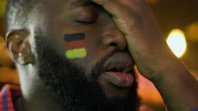Μαύρος οπαδός αθλήματος με τη γερμανική σημαία στο μάγουλο που ανατρέπεται για το αγαπημένο χάνοντας παιχνίδι ομάδων απόθεμα βίντεο