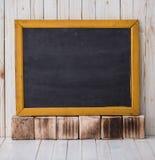 Μαύρος πίνακας κιμωλίας στο ξύλινο υπόβαθρο, που τοποθετείται οριζόντια στοκ εικόνα