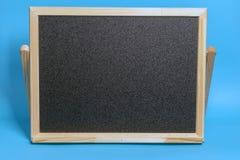 Μαύρος πίνακας σε ένα ξύλινο πλαίσιο σε ένα μπλε υπόβαθρο Πρότυπο για τις αγορές, πωλήσεις, μαύρη Παρασκευή στοκ φωτογραφία με δικαίωμα ελεύθερης χρήσης
