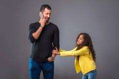 Μαύρος πατέρας που μιλά στο τηλέφωνό του ενώ η κόρη του που τραβά δικοί του Στοκ φωτογραφία με δικαίωμα ελεύθερης χρήσης