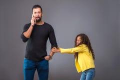 Μαύρος πατέρας που μιλά στο τηλέφωνό του ενώ η κόρη του που τραβά δικοί του Στοκ Φωτογραφία