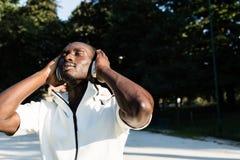 Μαύρος που ακούει τη μουσική σε ένα πάρκο πόλεων Στοκ Εικόνες