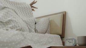 Μαύρος που κλείνει το συναγερμό το πρωί Νέος ενήλικος που ξυπνά στο κρεβάτι αργά απόθεμα βίντεο