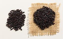 Μαύρος σπόρος ρυζιού Κλείστε επάνω των σιταριών που είναι εξαπλωμένων στον άσπρο πίνακα Στοκ Εικόνες