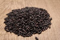 Μαύρος σπόρος ρυζιού Σωρός των σιταριών στον ξύλινο πίνακα Εκλεκτικό φ Στοκ Φωτογραφία