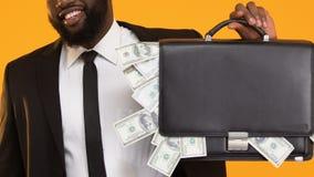 Μαύρος στο κοστούμι που παρουσιάζει χαρτοφύλακα με τα δολάρια και τους αντίχειρες επάνω, εύκολο κέρδος φιλμ μικρού μήκους