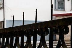 Μαύρος σφυρηλατημένος φράκτης κατά μήκος του κτηρίου κοντά επάνω στοκ εικόνες