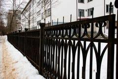 Μαύρος σφυρηλατημένος φράκτης κατά μήκος του κτηρίου κοντά επάνω στοκ φωτογραφία με δικαίωμα ελεύθερης χρήσης