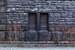 Μαύρος τουβλότοιχος με δύο κλειστά παράθυρα - υπόβαθρο Στοκ Φωτογραφία