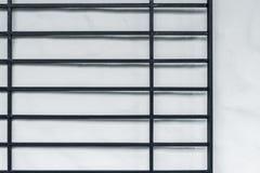 Μαύρος φράκτης σιδήρου στον άσπρο τοίχο στοκ φωτογραφίες