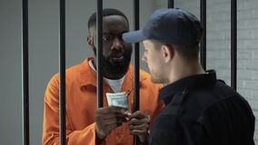 Μαύρος φυλακισμένος γκάγκστερ που δίνει τα μετρητά δολαρίων στο δεσμοφύλακα, δωροδοκία στη φυλακή απόθεμα βίντεο