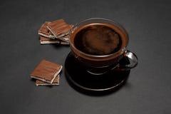 Μαύρος, φυσικός, ευώδης καφές στο διαφανές φλυτζάνι σε ένα μαύρο υπόβαθρο, με τη σοκολάτα γάλακτος στοκ εικόνα με δικαίωμα ελεύθερης χρήσης