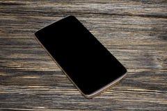 Μαύρο έξυπνο τηλέφωνο με την απομονωμένη οθόνη στο παλαιό ξύλινο γραφείο στοκ εικόνα