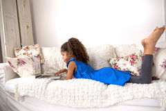 Μαύρο έφηβη που εγκαθιστά σε έναν καναπέ με ένα lap-top Στοκ εικόνες με δικαίωμα ελεύθερης χρήσης