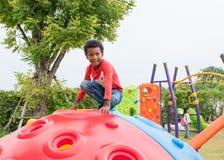 Μαύρο αγόρι παιδιών Αμερικανών που έχει τη διασκέδαση που παίζει στα παιδιά ` s climbin στοκ εικόνες