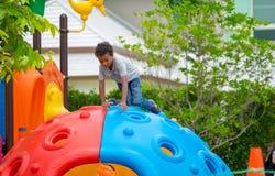 Μαύρο αγόρι παιδιών Αμερικανών που έχει τη διασκέδαση που παίζει στα παιδιά ` s climbin στοκ εικόνα