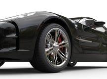 Μαύρο αθλητικό αυτοκίνητο πολυτέλειας στο άσπρο υπόβαθρο - στενός επάνω ροδών Στοκ Εικόνες