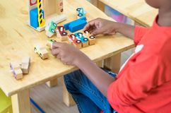 Μαύρο αμερικανικό παιχνίδι αυτοκινήτων παιχνιδιού παιδιών στην τάξη στον παιδικό σταθμό προ Στοκ εικόνα με δικαίωμα ελεύθερης χρήσης
