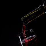μαύρο απομονωμένο γυαλί χύνοντας κόκκινο κρασί Στοκ Εικόνες