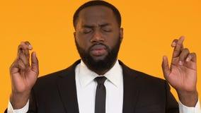 Μαύρο αρσενικό στο κοστούμι που διασχίζει τα δάχτυλα για την καλή τύχη, που ελπίζει να κερδίσει, πίστη στο καλύτερο απόθεμα βίντεο