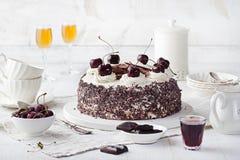 Μαύρο δασικό κέικ, που διακοσμείται με την κτυπημένη πίτα κρέμας και Schwarzwald κερασιών, τη σκοτεινά σοκολάτα και το επιδόρπιο  στοκ εικόνες