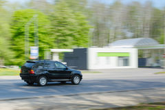 Μαύρο αυτοκίνητο στην κίνηση στο δρόμο ασφάλτου και τα πράσινα δέντρα Στοκ Εικόνες